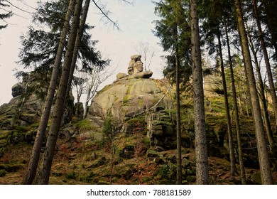 Specific original rocky formation in the mountains with atypical shape of stones laying on top with trees around it in the forest while hiking with bunch of friends, sport recreation time