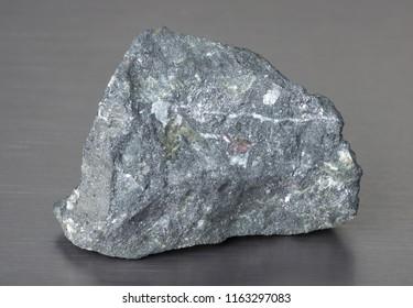 Specimen of mineral stone magnetite (lodestone) on gray background.