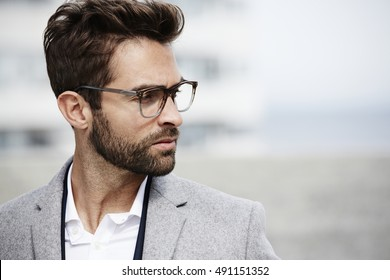 Spectacled businessman looking away