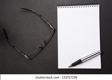 Spectacles and writing pad with lots of copy space