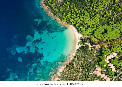 Spectacular aerial view of a beautiful wild beach bathed by a clear and turquoise sea, Sardinia, Italy.