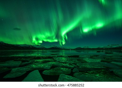 Spectacular auroral display over ice sea at night ,Iceland