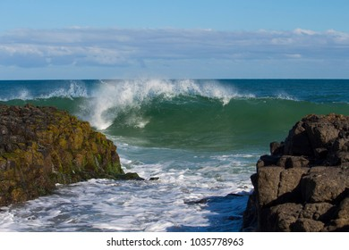 Spectacular backwash from the  Indian Ocean waves breaking on basalt rocks at  Ocean Beach Bunbury Western Australia on a sunny morning in late winter  sends salty spray high into the air.