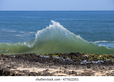 Spectacular backwash from the  Indian Ocean waves breaking on basalt rocks at  Ocean beach Bunbury Western Australia on a sunny morning in early spring  sends salty spray high into the air.
