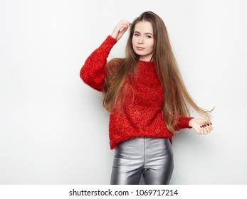 Spectacular blonde woman in red blouse silver leather pants posing in front of white wall. Graceful girl gorgeous long hair having fun on photoshoot.