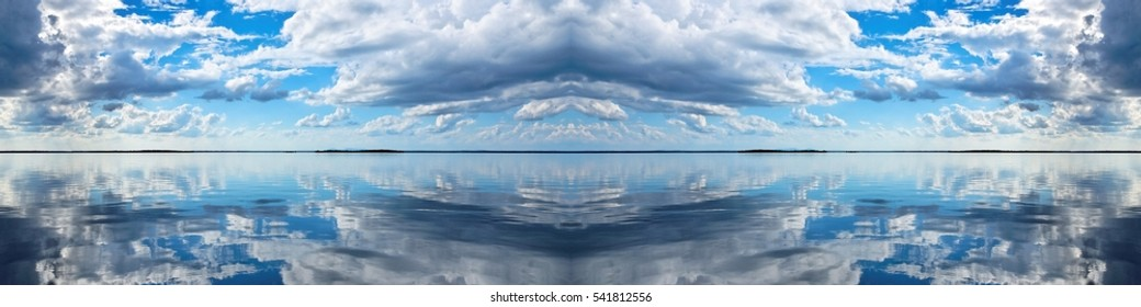 Spectacular blue and white panoramic Cumulus cloudscape with clear water reflections. Photograph was shot at sea from the deck of a boat looking toward land.