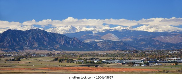 the  spectacular Boulder FlatIrons and snow-capped front range of the colorado rocky  mountains on a sunny fall day with a pumpkin patch in the foreground, as seen from broomfield, colorado