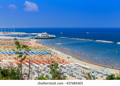 spectacular and colorful view of the beaches of the Marche region in Italy papered by umbrellas in rows in seaside resorts