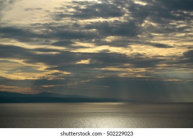 Spectacular dramatic dark sky with clouds over grey sea horizon on evening seascape on natural background