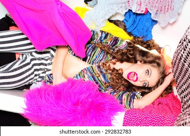Spectacular emotional young girl with curly hair lying in white bathtub amid colorful clothes pink orange red blue colors on grey wall background, horizontal picture