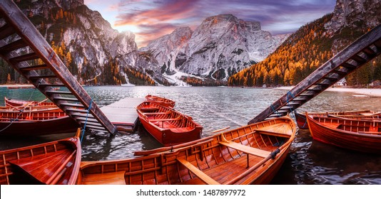Spectacular famous place with typical wooden boats on the alpine lake Braies in Dolomites. Impressive Lago di Braies during sunset. Amazing Autumn nature landscape. Iconic location for photographers
