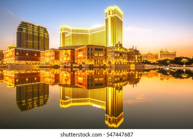 Spectacular golden skyline of Macau in China, reflected in the water at twilight.