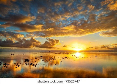 A spectacular golden sunset seen from Reunion Island reflected on the calm surface of the Indian Ocean.