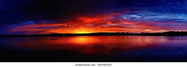 A spectacular inspirational brightly coloured stratocumulus cloudy sea water tropical panoramic sunrise seascape featuring striking ocean water reflections, Queensland, Australia.