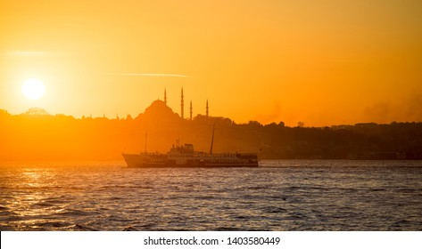 Spectacular Istanbul silhouette at sunset. Minarets silhouette of Istanbul Suleymaniye Mosque with old ferry (steamboat) at sundown on the Bosphorus.