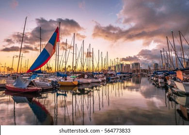 Spectacular landscape of boats and yachts docked at the Ala Wai Harbor, the largest yacht harbor of Hawaii, reflecting in the sea at sunset. Honolulu, Oahu in Hawaii, United States.