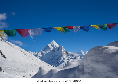 Spectacular landscape of snowcapped Himalaya mountains with Nepali traditional colorful buddhist prayer flags near Everest base camp in Nepal
