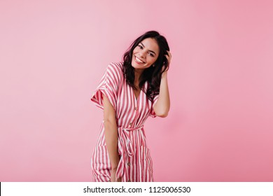 Spectacular latin young woman playing with her brown hair. Indoor photo of wonderful female model isolated on pink background.