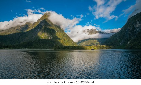 Spectacular mountain range surrounded by clouds close to sunset in Milford Sound, a fiord in the southwest of New Zealand's South Island. A boat cruise is also a very popular attraction here.