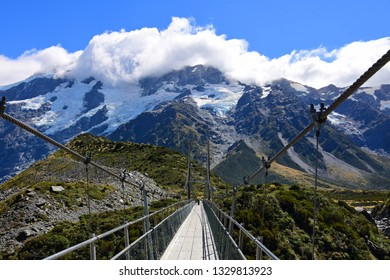 spectacular  mountain  scenery and a suspension bridge on the hooker river on a sunny day in summer along the hooker valley track near mount cook village on the south island of new zealand