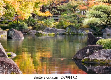 Spectacular nature and autumn colors reflected in the pond bordered by rocks covered in moss at Koko-en Gardens in Himeji, Japan.