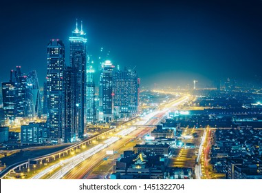 Spectacular nighttime skyline of a big modern city at night. Dubai, UAE. Aerial view on highways and skyscrapers.