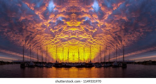 Spectacular non urban coastal , orange and yellow cloud, grey blue sky, sunset landscape. With mostly altocumulus clouds over water and a seashore horizon, viewed from the ocean. Australia.