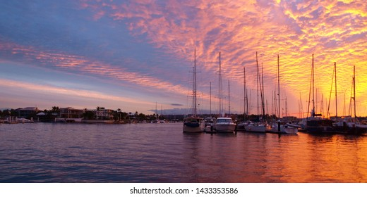 Spectacular orange and golden yellow stratocumulus cloudy tropical marina sunset seascape with colourful water reflection in protected waters at Mooloolaba, Queensland, Australia.