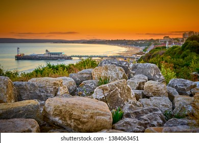 Spectacular picturesque sunset view from the cliff rocks formation, overlooking artistically defocused Bournemouth Beach and Pier in the foreground. Dorset England UK Europe