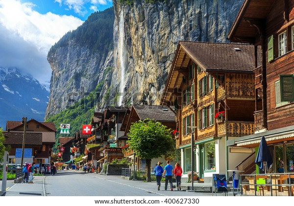 Spectacular principal street of Lauterbrunnen with shops,hotels,terraces,swiss flags and stunning Staubbach waterfall in background,Bernese Oberland,Switzerland,Europe