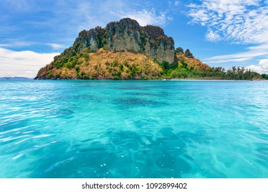 Spectacular scenery the tropical island with the limestone cliffs covered with the vegetation in the crystal clear ocean next to the exotic Phi Phi Islands, the Kingdom of Thailand. Paradise image.