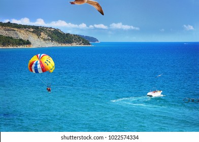 Spectacular scenic view on picturesque bay with people flying on a colorful parachute towed by a motor boat. Parasailing water amusement.