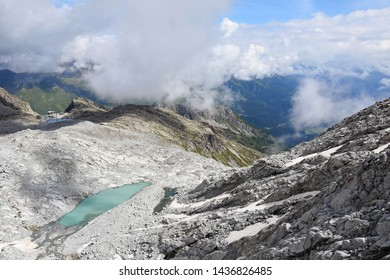 Spectacular summer view from the top of Presena Glacier, foreground showing a green glacial melting water lake while the middle station cableway, Monticello lake and Tonale Pass in background, Italy