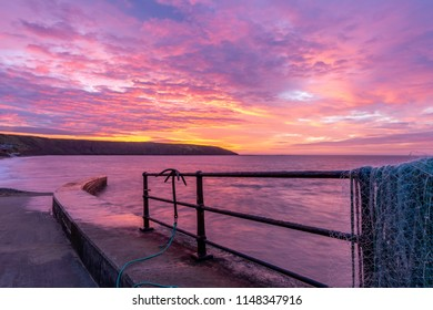 A spectacular sunrise looking towards Filey Brigg at high tide from the fishing jetty, Filey, North Yorkshire, England