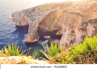 Spectacular sunset at the famous natural limestone arch of Blue grotto on Malta, Europe