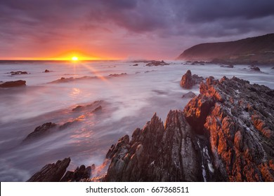 Spectacular sunset over the rocky coastline of the Tsitsikamma section of the Garden Route National Park, South Africa.