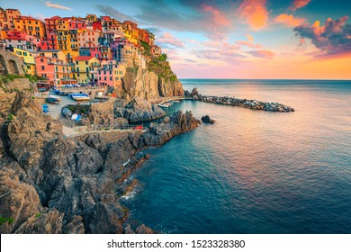 Spectacular travel and photography location. Stunning touristic village with colorful houses on the cliffs at sunset, Manarola, Cinque Terre, Liguria, Italy, Europe