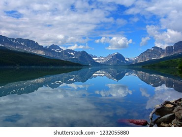 spectacular view across lake sherburne on a sunny day, of the peaks  in glacier national park, montana