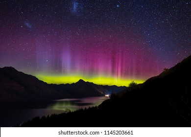 Spectacular view as aurora lights up the sky of Queenstown, New Zealand. When particles from a solar storm reached our Earth, it creates an array of colored lights as they hit the atmosphere.