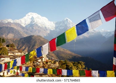 Spectacular view of grand snow capped summits of the Himalayan mountain range rising above in background, with rows of colorful Buddhist prayer flags strung along mountain passes in foreground