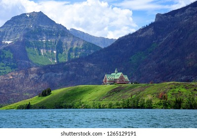 spectacular view  of the iconic prince of wales hotel and the canadian rocky mountains  across the turquoise-colored waterton lakes in summer, in waterton, alberta,  canada