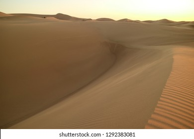 Spectacular view of the immense sand dunes with group of people and dune buggy in distance, Huacachina desert, Ica, Peru, South America