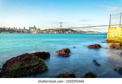 The spectacular view of Istanbul Bosphorus Bridge on the Kuzguncuk rocky beach in Uskudar. Kuzguncuk is a neighborhood in the Uskudar district in Istanbul.