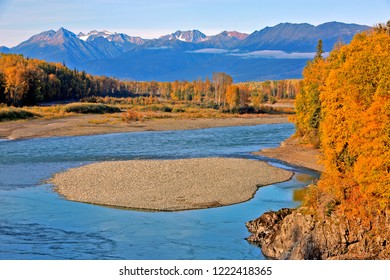 Spectacular view of the Kispiox Valley, with the clean blue river running along a forest in prime autumn colors and beautiful Mountain peaks in the background.
