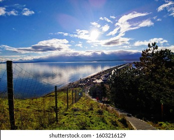 Spectacular view on a bright, sunny day at the top of a long staircase. Blue sky, white clouds, sun shining over a long spit of land straddled by ocean water. Goose Spit Park, Comox Valley, BC, Canada