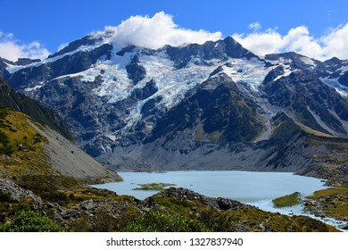spectacular view of rugged mountain peaks and a glacial lake  along the hooker valley track in summer, near mount cook village, on the south island of new zealand
