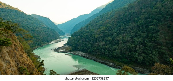 Spectacular view of the sacred Ganges river flowing through the green mountains of Rishikesh, Uttarakhand, India.