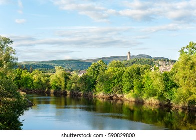 The spectacular view of scottish nature with National Wallace Monument tower standing on the summit of Abbey Craig on background Hilltop near Stirling in Scotland. Colored horizontal outdoors image.