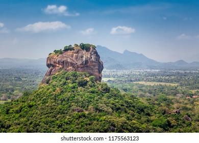 Spectacular view of the Sigiriya Lion rock surrounded by green rich vegetation. Sigiriya is photographed from Pidurangala mountain in Dambula, Sri Lanka.