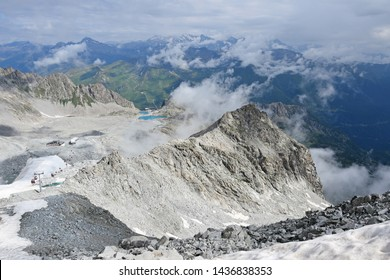 Spectacular view from the top of Presena Glacier towards ski slope and middle station cableway, with Monticello lake and Passo del Tonale mountain pass in background, summer hiking in northern Italy